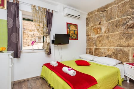 Sunny room with a private shower, on the 1st floor of a picturesque Dalmatian stone house in the Diocletian's palace. Northern wall of the apartment is actually an ancient Palace wall, which adds additional value to the already charming space.