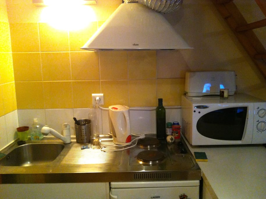 Cuisine comprenant : un frigo, des plaques de cuisson, un micro-ondes, une bouilloire, les ustensiles et couverts