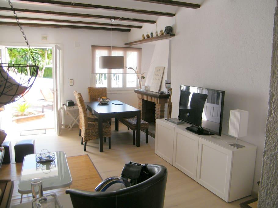 Wohnzimmer mit Ledersofa, Ledersessel und Esstisch für 6 Personen.