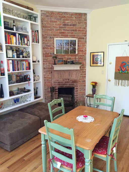 Original brick fireplace, dining table, bookcase, and front door.