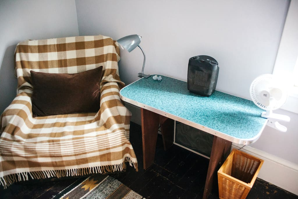 Sitting area with comfy chair, small desk/work table, reading light, space heater, and fan.