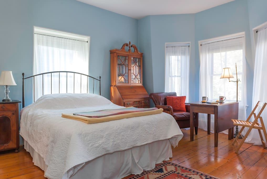 Queen-sized bed in bright and airy room.