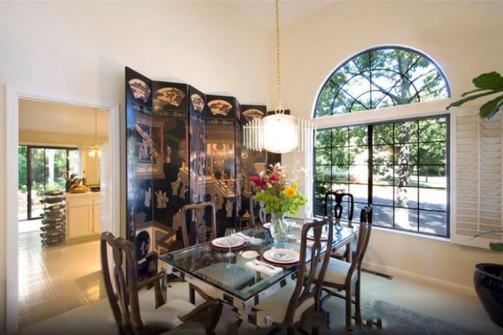 The dining room showcases an antique, oriental Coromandel screen,  glass table with seating for six, and a large window allowing plenty of sunlight!