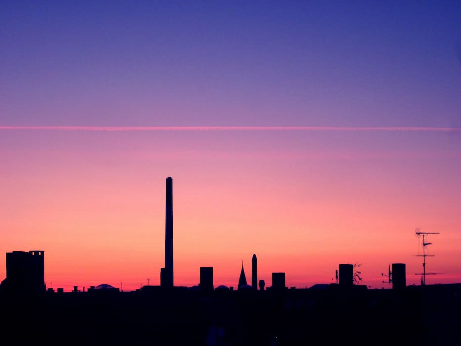 Clear chimney-top skyline view over Copenhagen with lots of sunsets