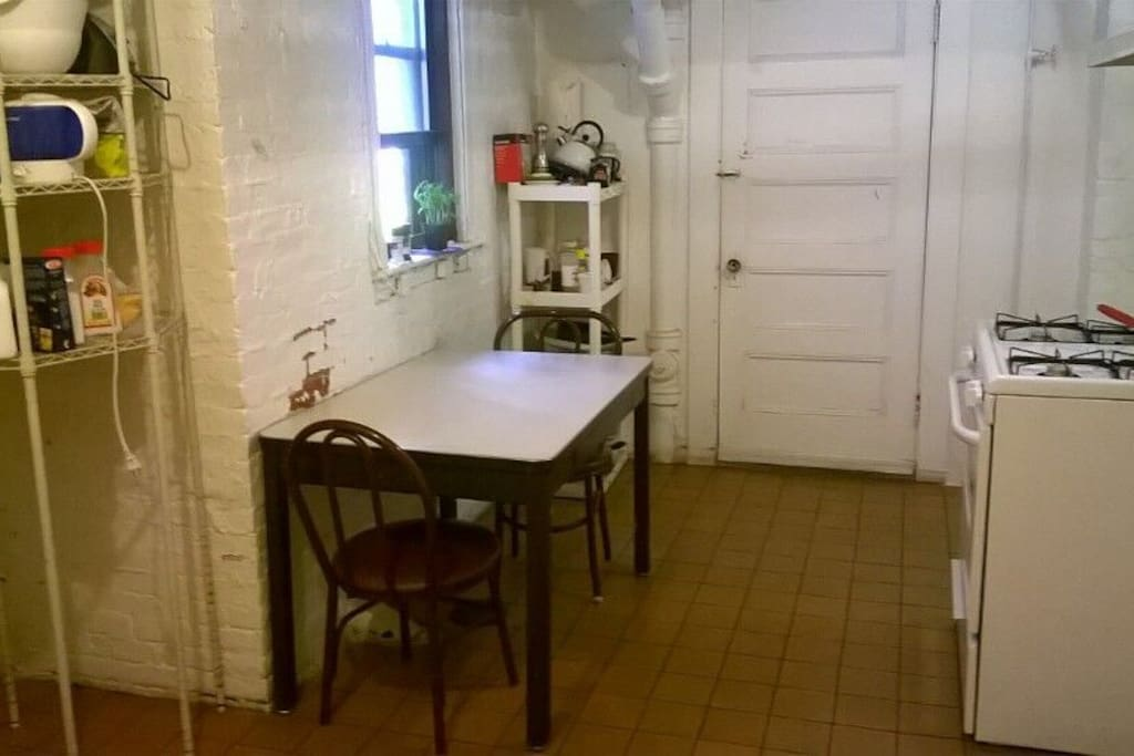 The public kitchen with a table (available for 6 people) a stove & oven, and a fridge.