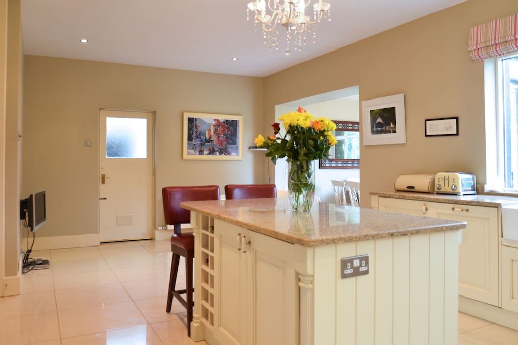 Large Island unit with comfortable leather stools, sockets and built in wine rack.