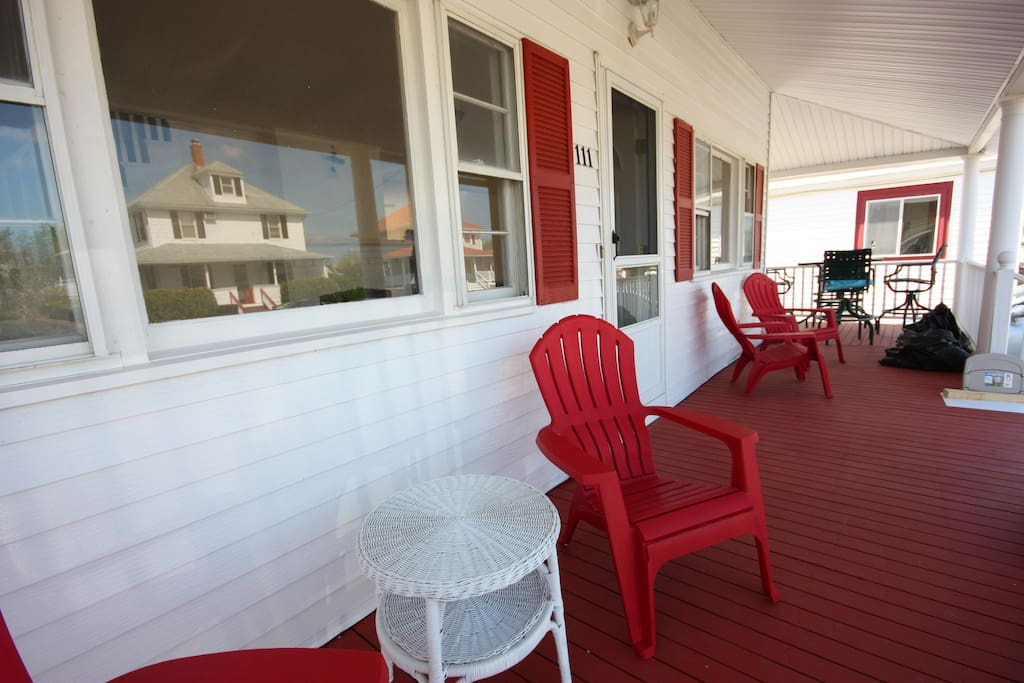 Large and comfortable front porch with plenty of seating and a high-top table for dining