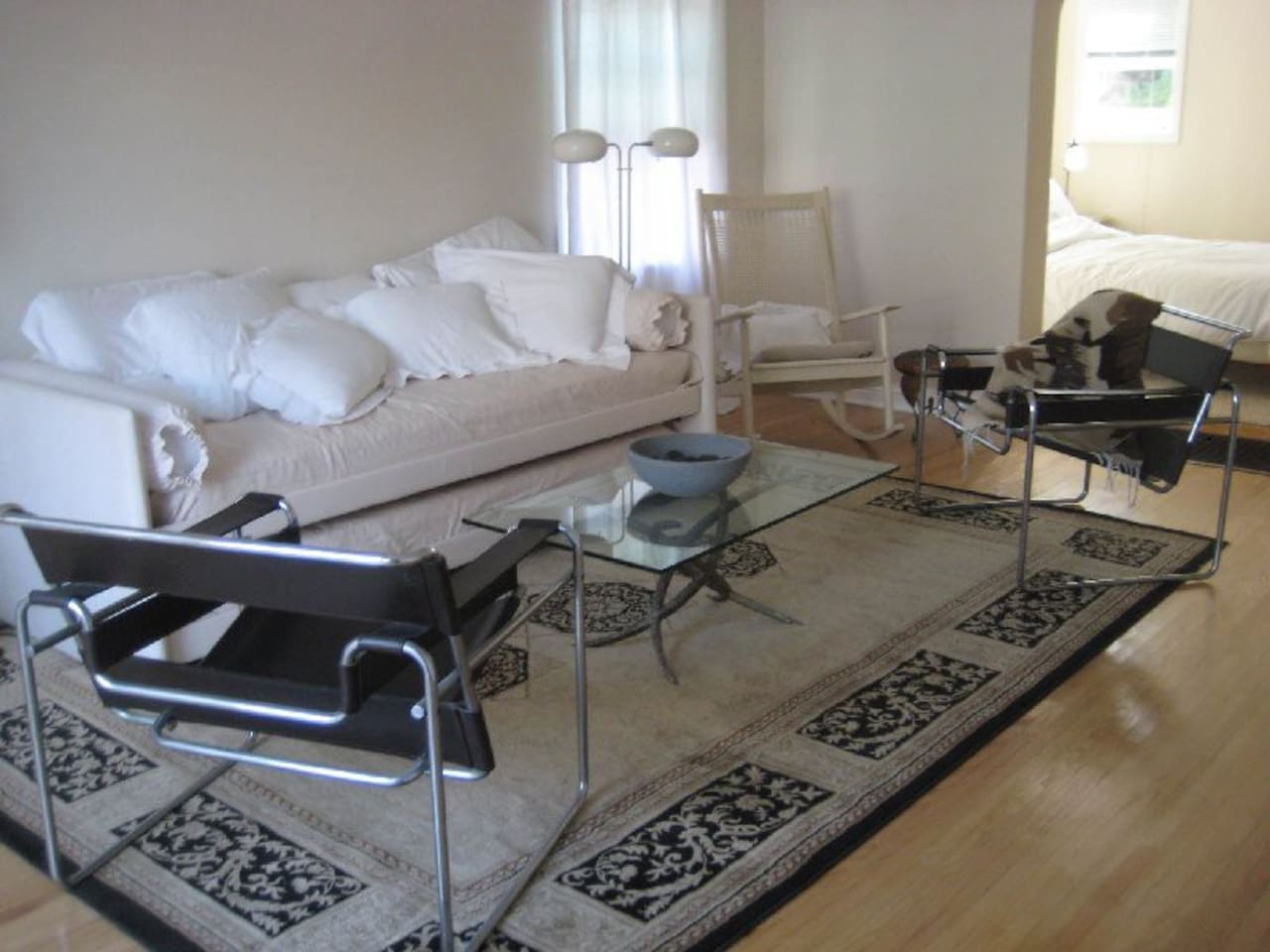 Living room features Italian-made, slide out twin-bed/sofa for family, friends in tow; authentic Wassily chairs; wicker rocker.