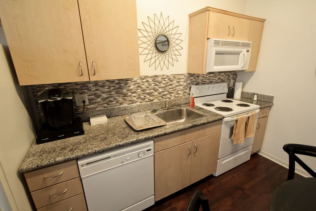Kitchen with Keurig coffee maker. Complimentary coffee, sugar, and cream are provided. Assortment of condiments and cooking ingredients are also provided.