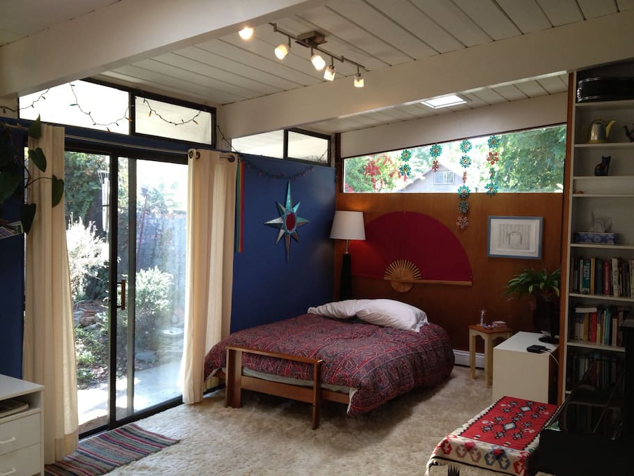 Guest bedroom filled with natural light and view to garden area.