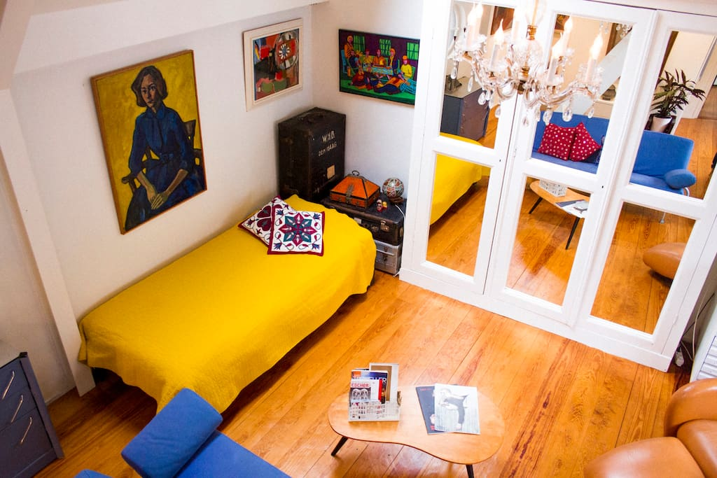 Guests sleep in a loft overlooking the seating area & single bed.