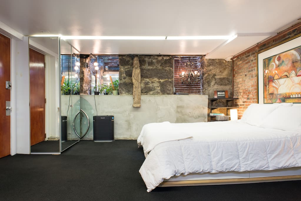 Queen Bed Window Wells, Mirrored Wardrobes and Exposed Brick