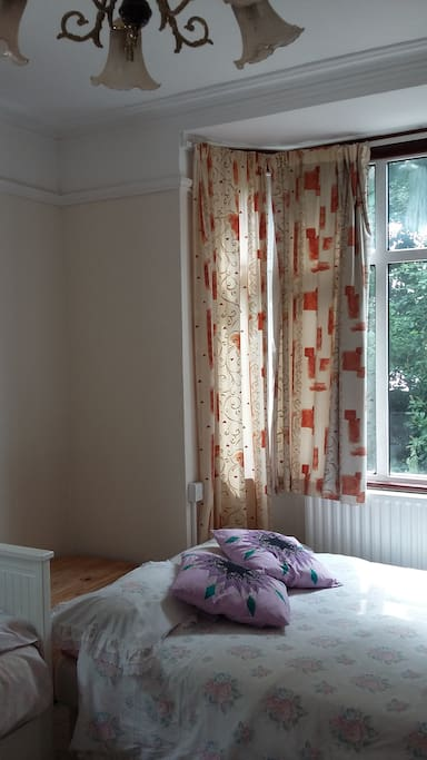 View of double bed and picture window looking out onto the park
