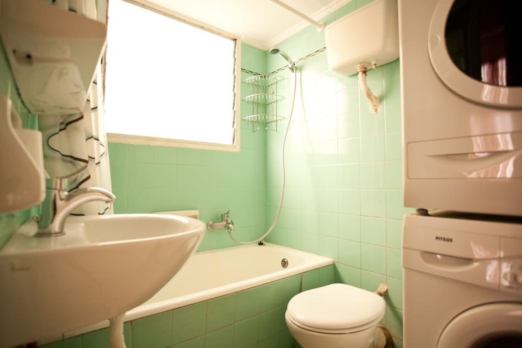 A large bathroom with tub and washing  machine - very clean . Shampoo and soap are provided for my guests