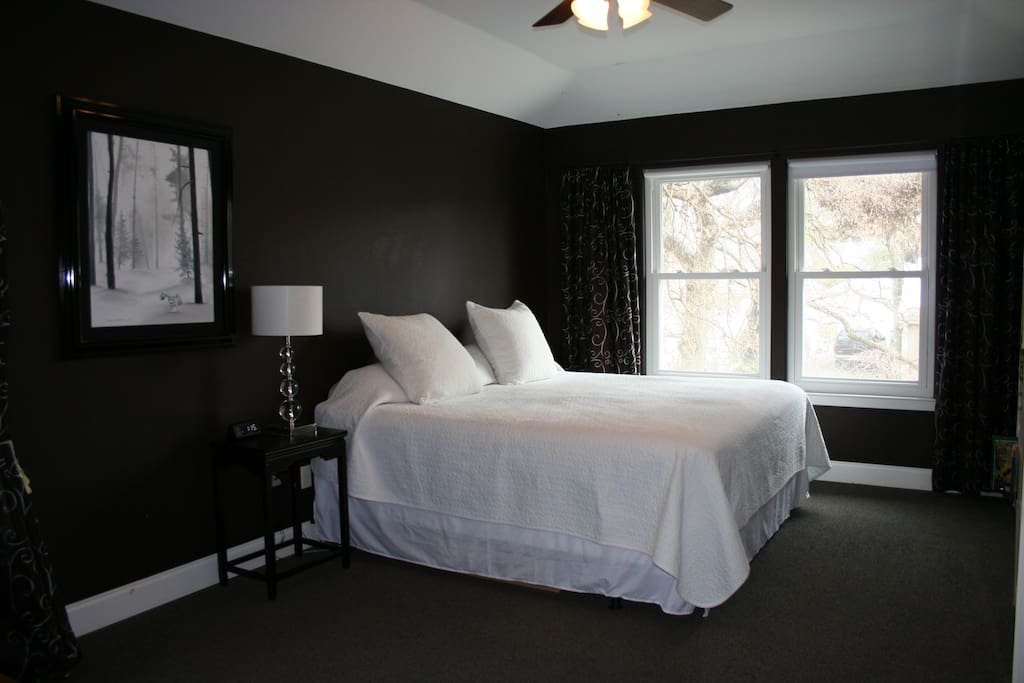 Master bedroom with bookshelves lining wall opposite king sized bed.