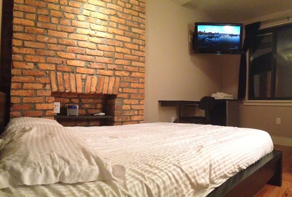Overview of bed, desk, night-time nook, and wall mounted TV.