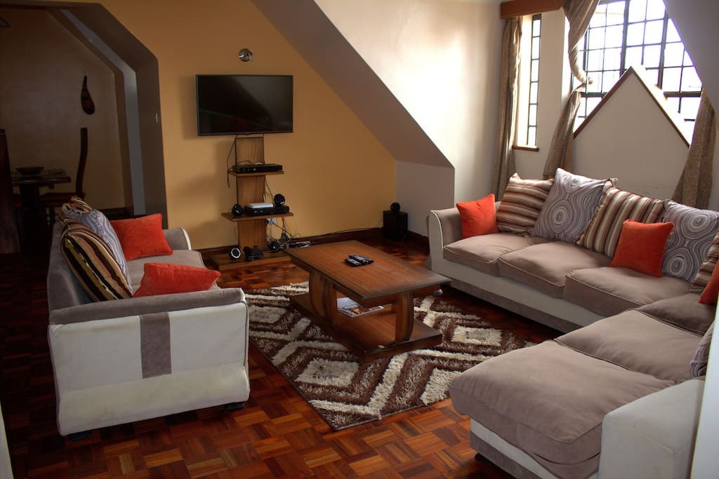 Comfy Living Room Area opening to the kitchen area with cathedral type windows allowing fresh breeze from Ngong Hills