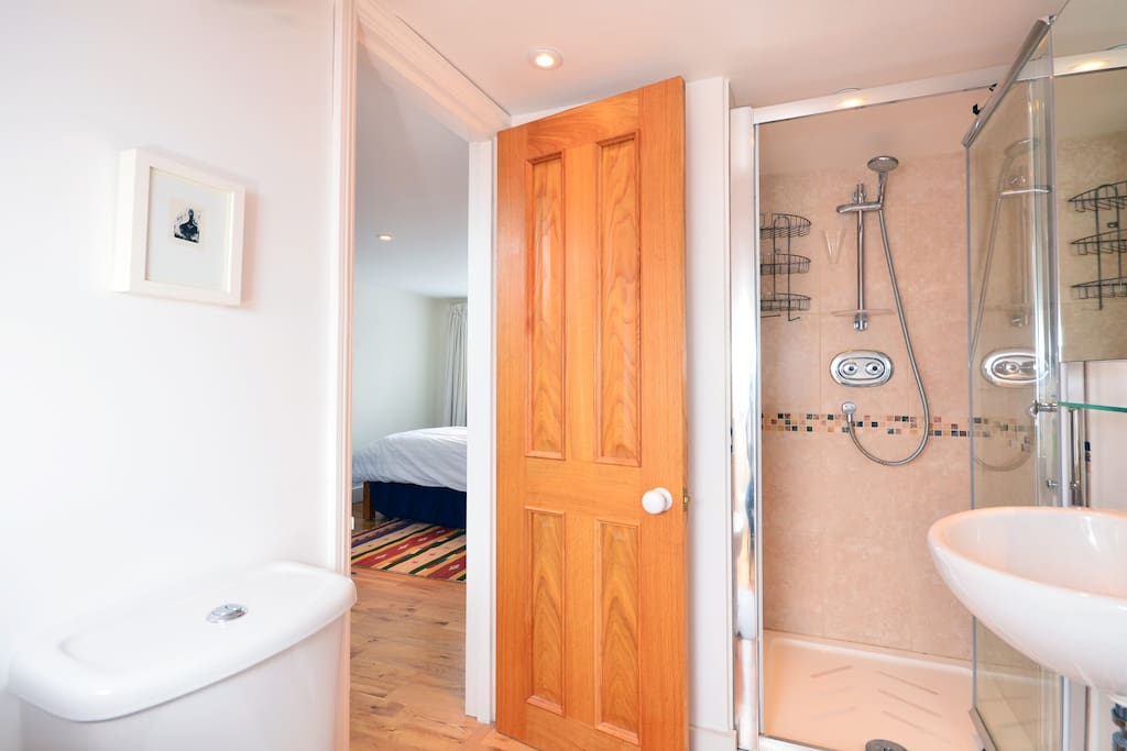 Warm oak flooring and stone tiled modern shower