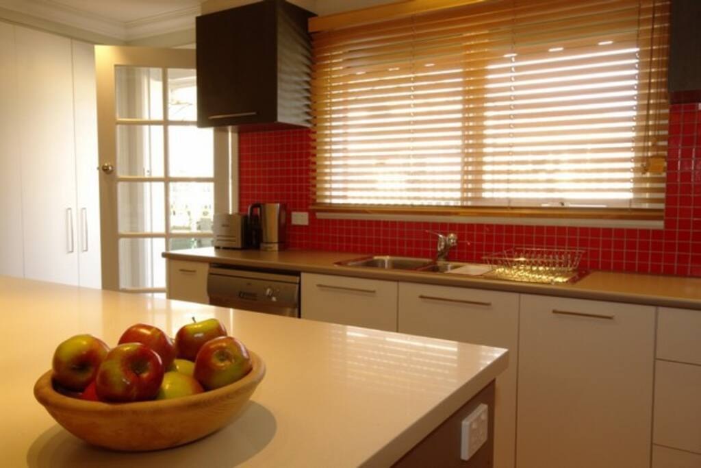 The kitchen door leads to the back terraced area, which includes a BBQ