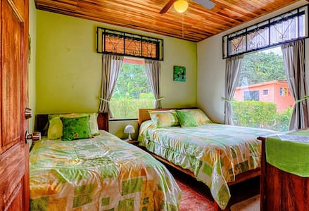 Lovely Private Room, has a Great View of the Rainforest, Tropical Garden, Arenal Lake and Volcano. Sleeps 3. Double & Twin Beds with Memory Foam Toppers. Close to all Adventure Activities. Use of Full Guest Kitchen & Common Areas. Bath Down the hall