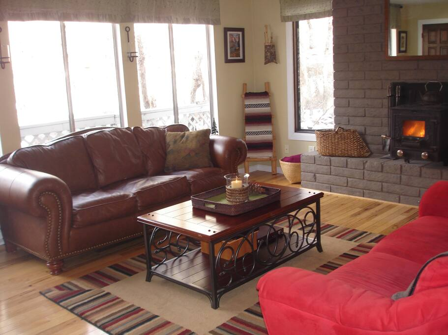 Cozy living room with woodstove. Large windows bring you close to nature.