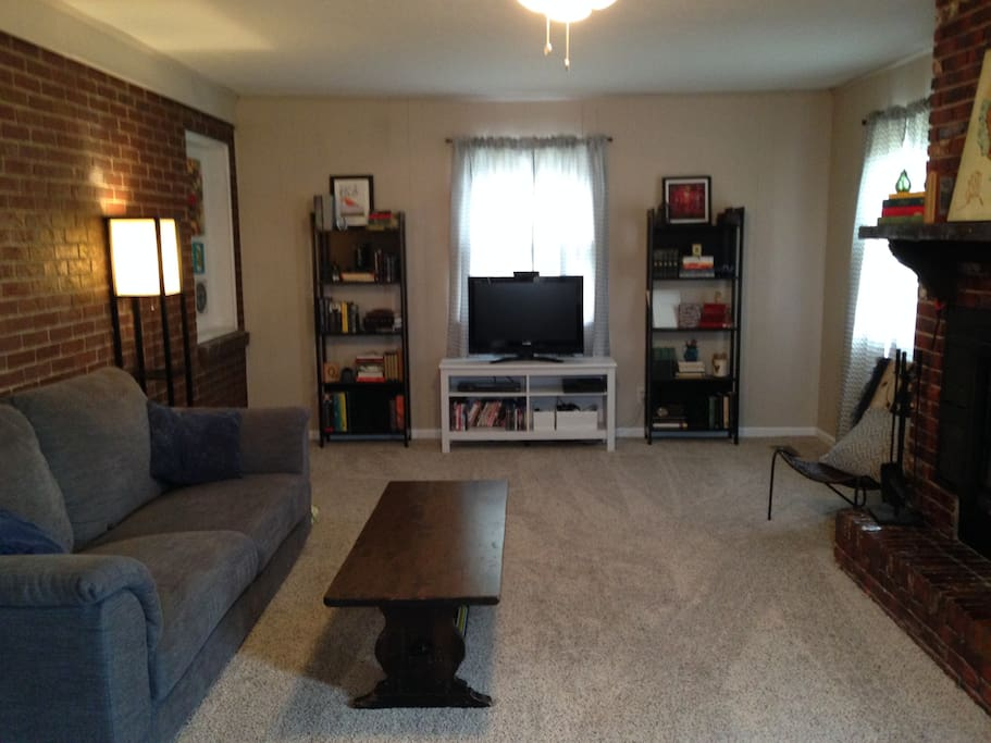 Spacious family room with TV, couch, and 3 reading chairs.