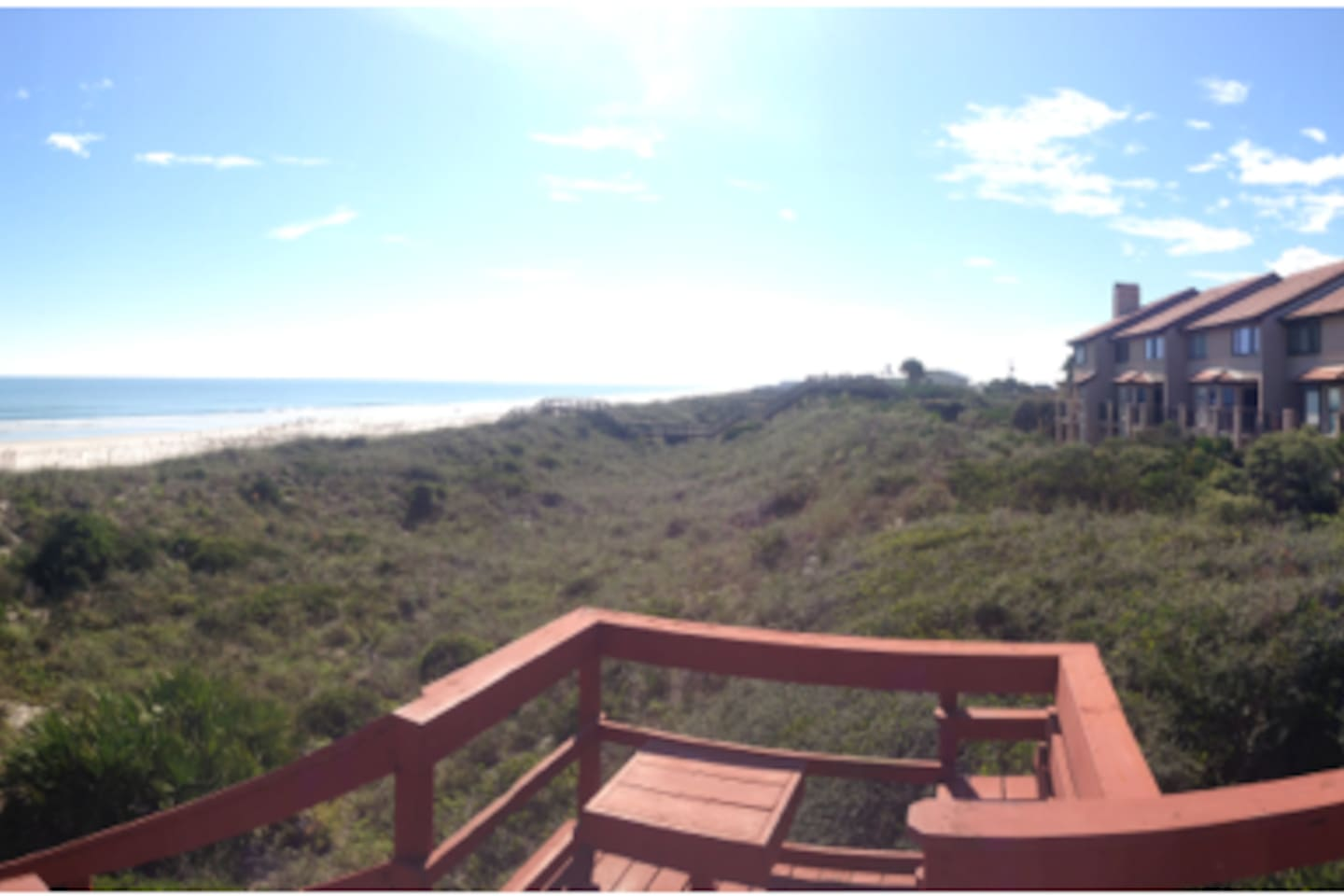 A view from the boardwalk.  the dunes, sandy beach, condo and ocean.