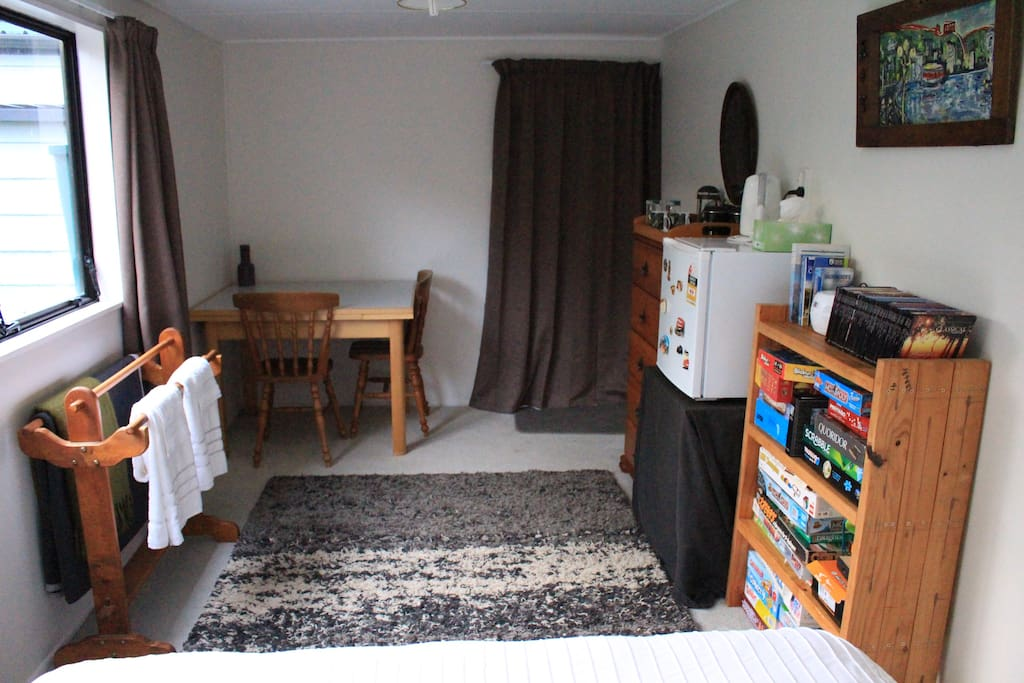 Dining table, small fridge and drawers with shelves full of board games and books!