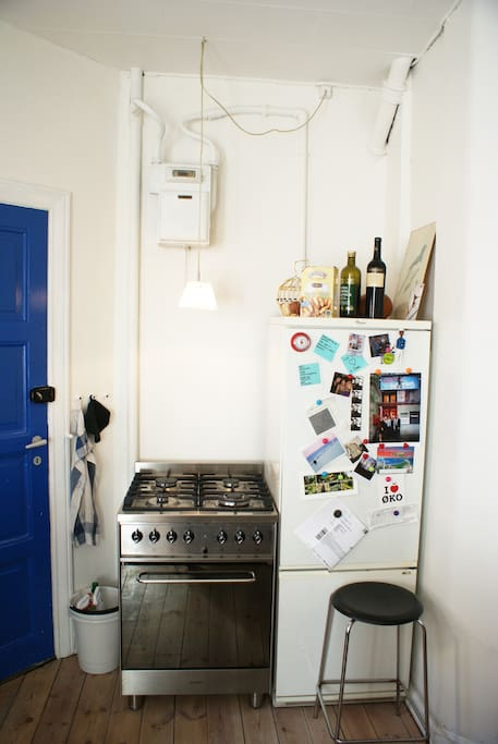 Kitchen. Back door, gas stove and refrigerator. (The fridge is replaced with a brand new one since this photo was taken).