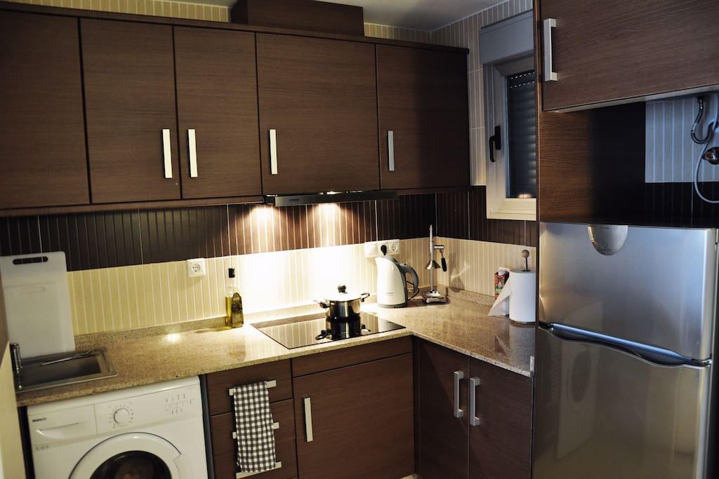 В Вашем распоряжении на кухне: комплекты посуды и бокалов на 6 персон, посуда для приготовления, электрическая плита и духовой шкаф (нет на фото), холодильник, посудомоечная машина (установлена вместо стиральной машины на фото), кофемашина Nespresso, электрическая соковыжималка и пресс для цитрусовых, профессиональный погружной блендер
