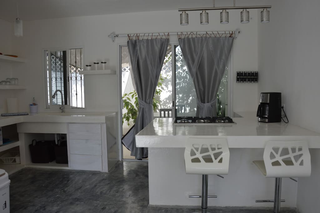 Kitchen island with oven and stove top.  Behind the island i the rear private patio, perfect for breakfast.