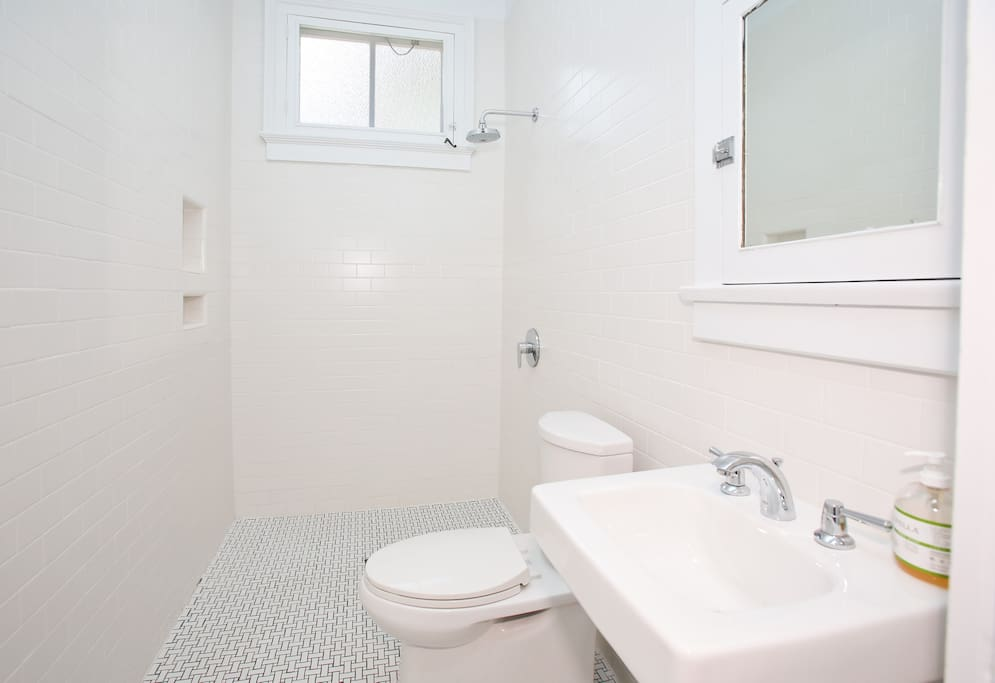 The bathroom is floor to ceiling tile with a walk in shower.