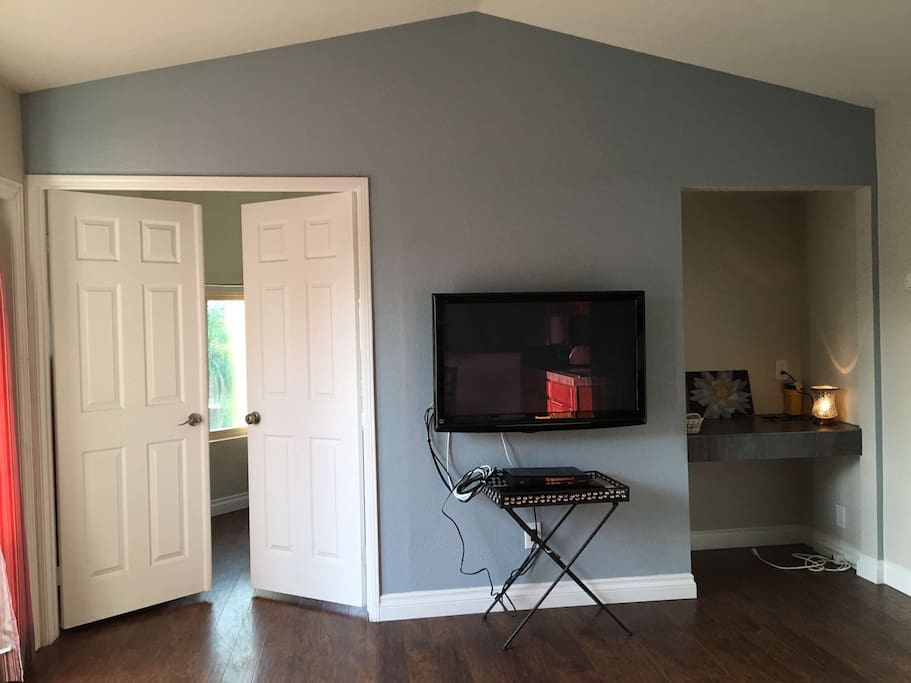 French doors leading to bedroom, office space and smart tv