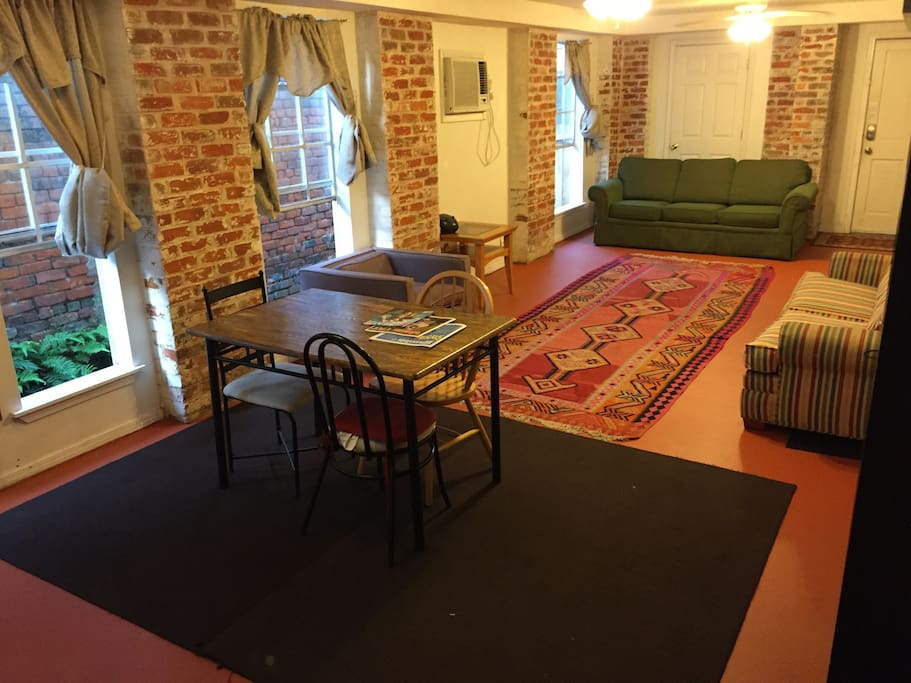 Huge living room with dining area and two fold out sofas.  Small private side yard outside windows.