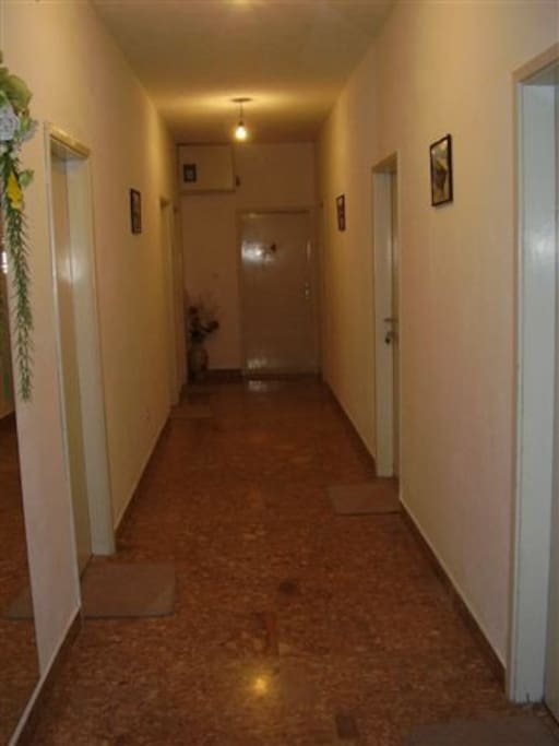 The entrance of the room is at the end of the hallway