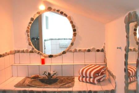Kingsize bed in loam rendered room - Aamiaismajoitus