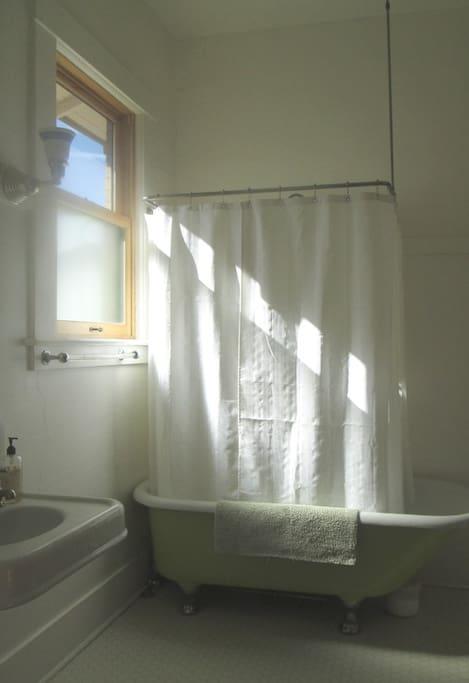Original 1909 bathroom is adjacent to the bedroom.