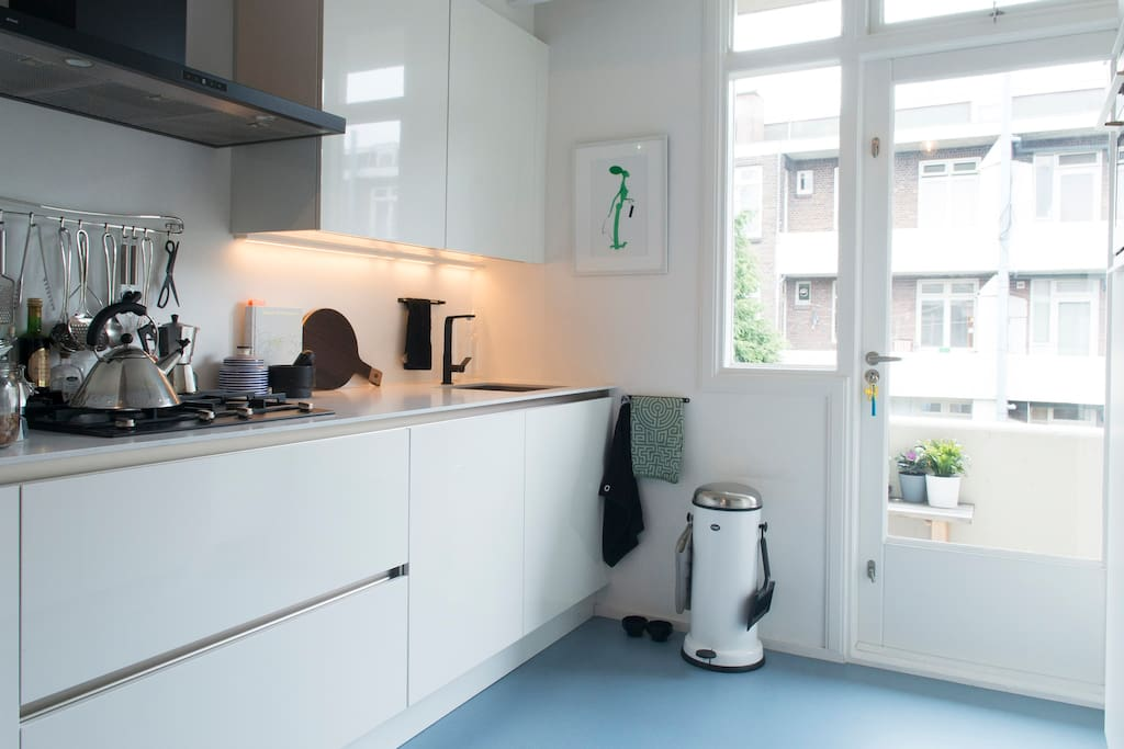 Spacious kitchen with microwave, oven, dishwasher and fridge. Access to the back balcony.