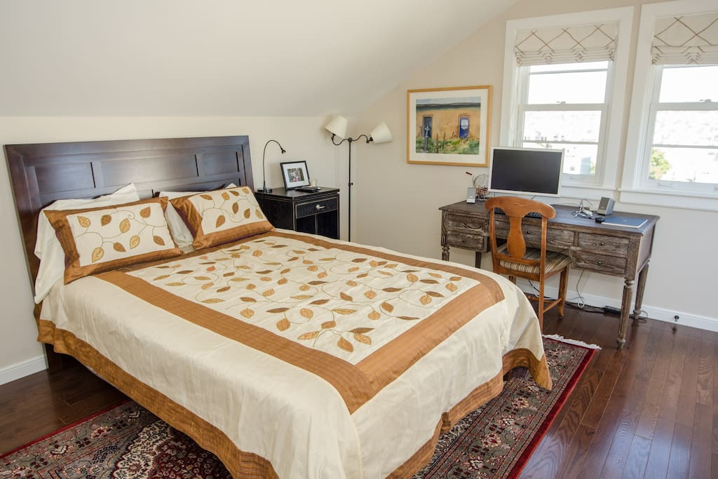 Charming bedroom features comfortable queen bed, desk, views, and storage