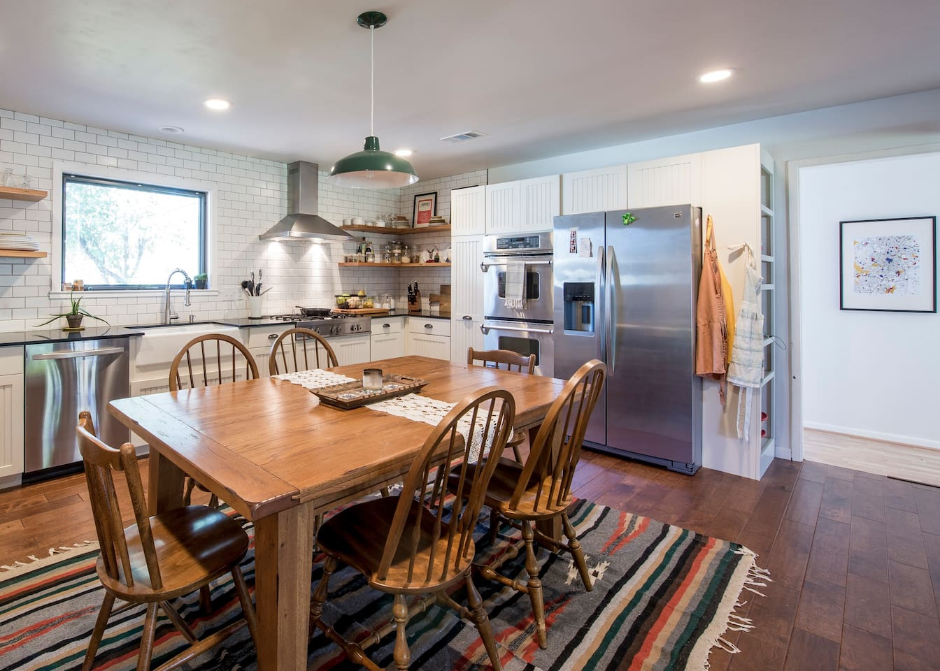 Our brand new kitchen featuring 6-burner gas rangetop, double oven, farmhouse sink, and a table that comfortably seats 10.