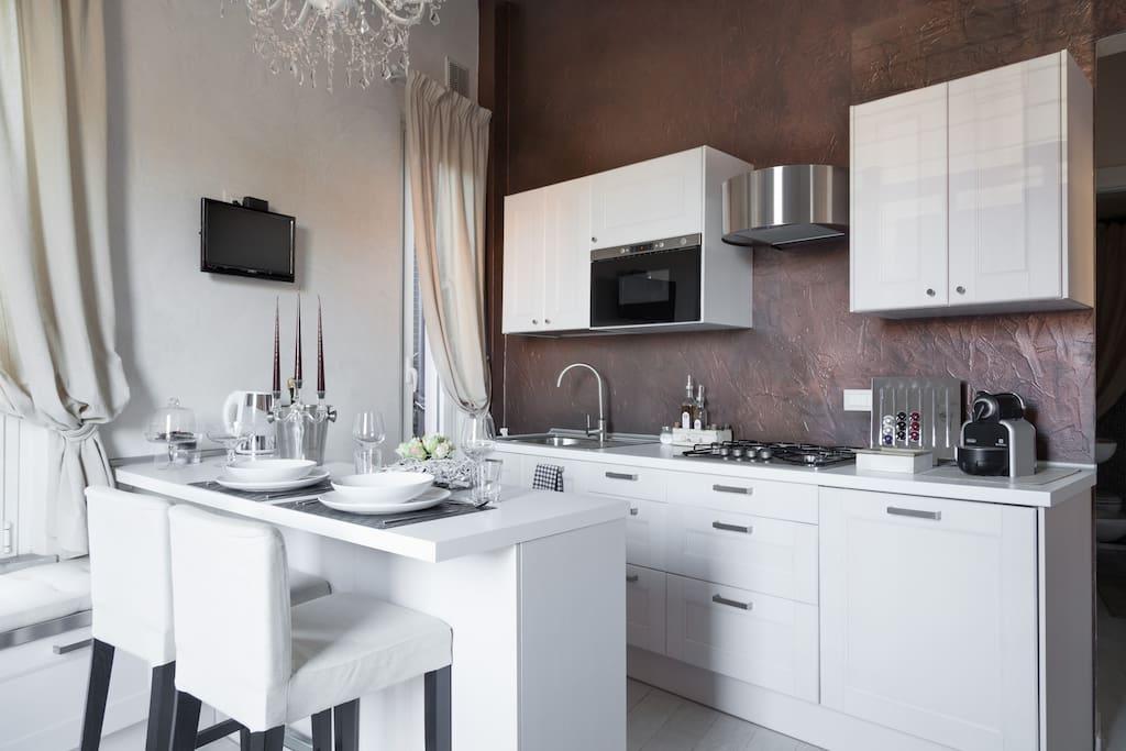 La cucina con il bancone: parete fatta in resina materica e ogni cosa per sentirsi come a casa