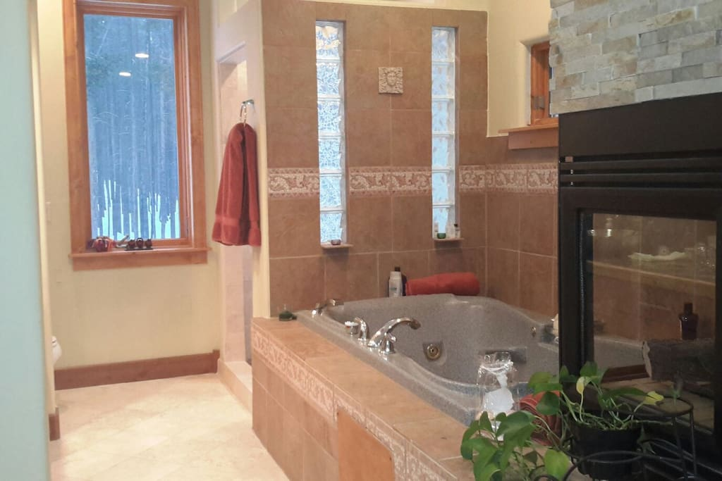 Spacious Jacuzzi tub for two with glass brick shower in background