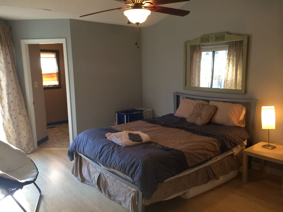 Master bedroom has queen sized bed, sliding glass door to raised back porch, walk in closet, ceiling fan, and private full bathroom.