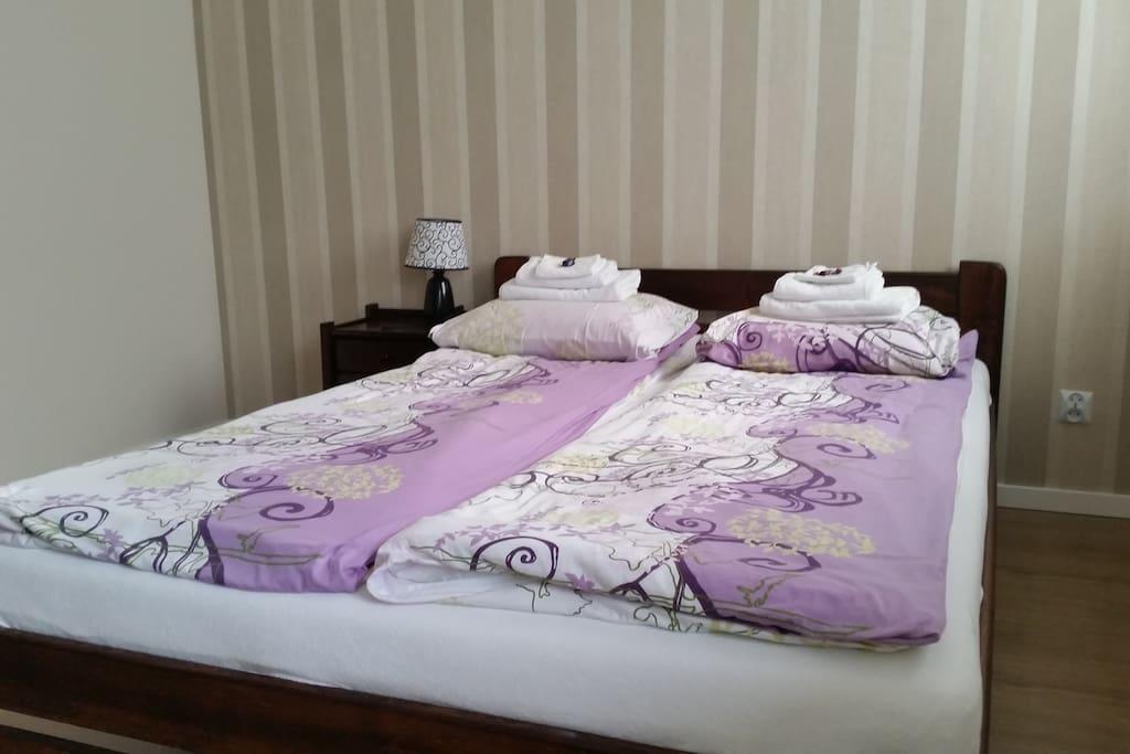 Podwójne łóżko ze zestawem ręczników dla każdego z Gości.