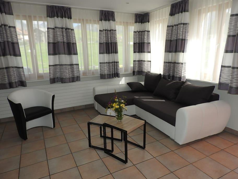 Sehr helles Wohnzimmer mit rundum Fenster in die Engadiner Berge