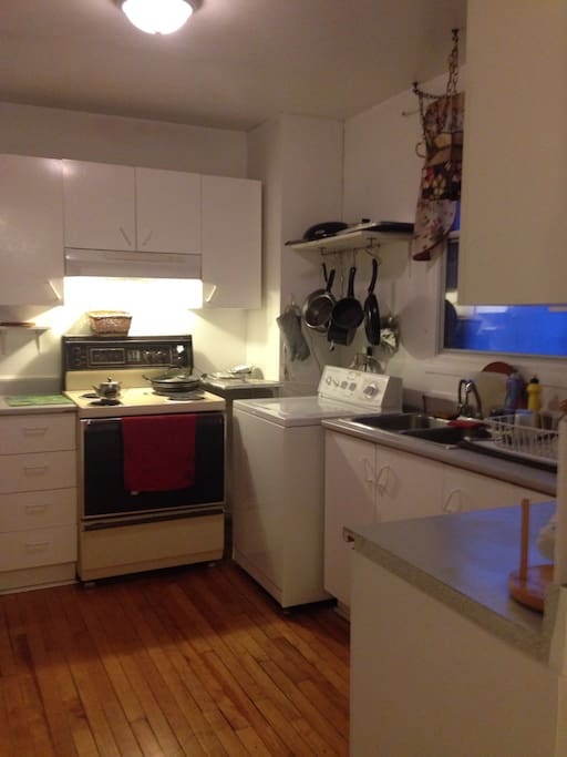 The kitchen is fully stocked with appliances, washer and dryer
