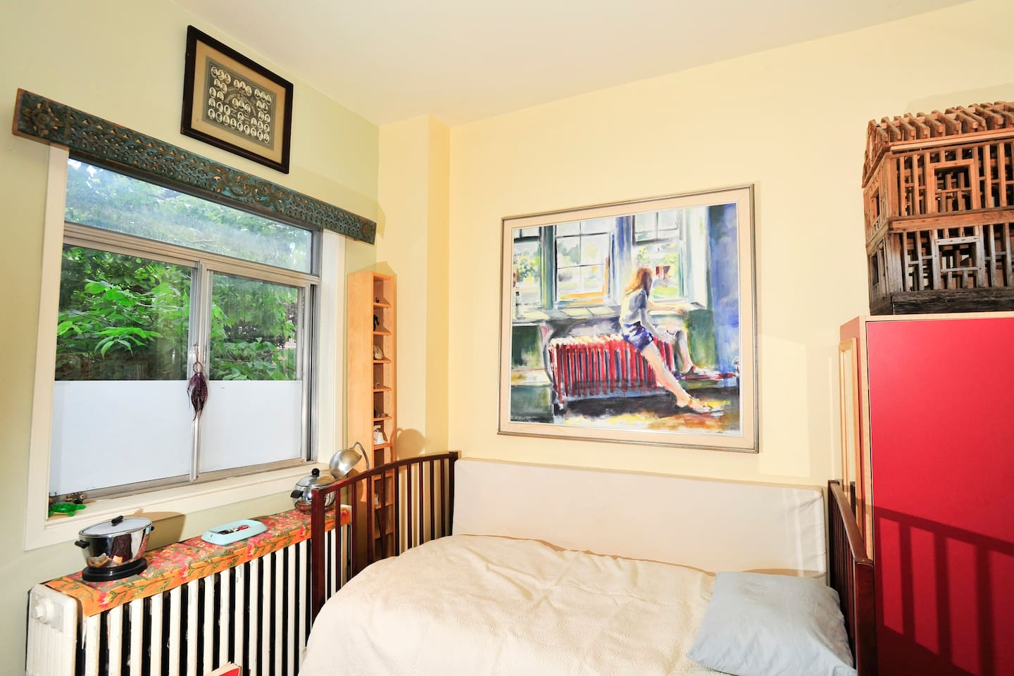 Serene room with trees outside the window and surrounded by art.