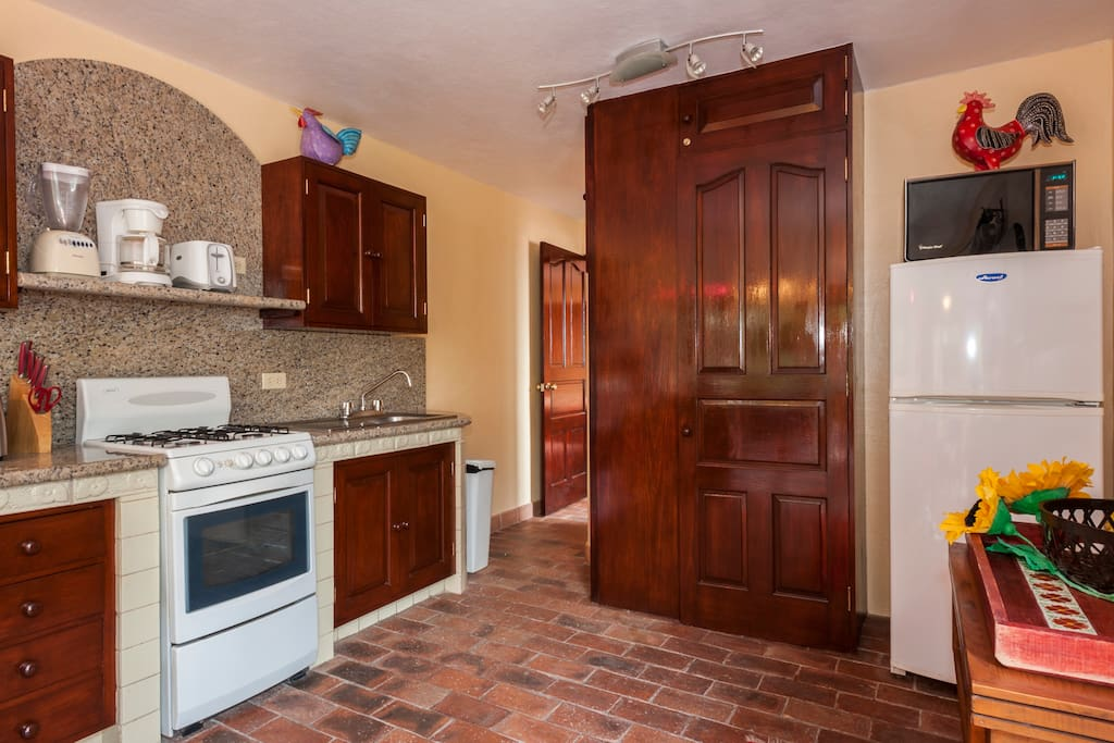 Kitchen with granite countertops and backsplash is equipped with the  gear our guests use, ample pantry space and applicance storage off the counter work surface.  Shelf above stove includes a convenient plug so you can recharge your  electronics from there, too.