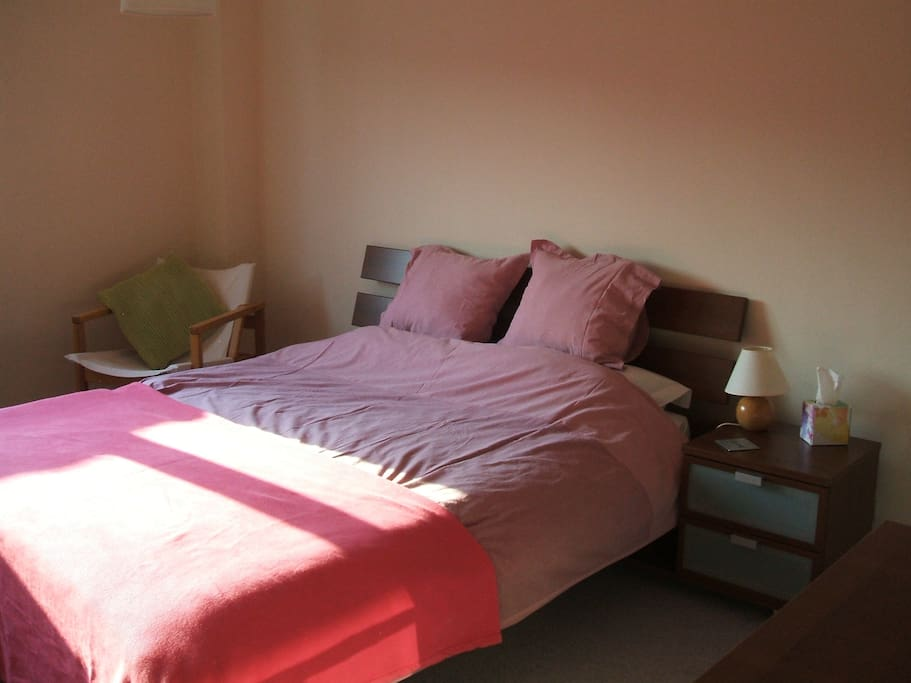 Comfortable double bed in large sunny room