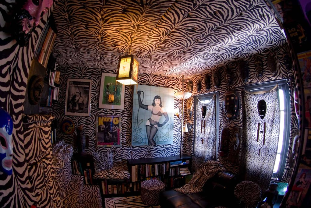 The zebra guest room for rent with lots of artwork and African masks.